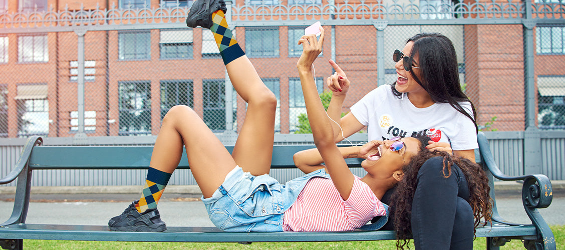Woman laying on park bench wearing shorts and socks - How to Style Crew Socks