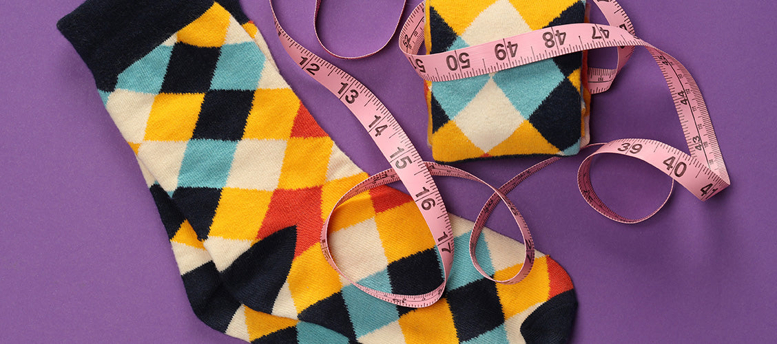 Colorful checker socks laying flat with measuring tape wrapped around them - How to Tell if Your Socks Fit