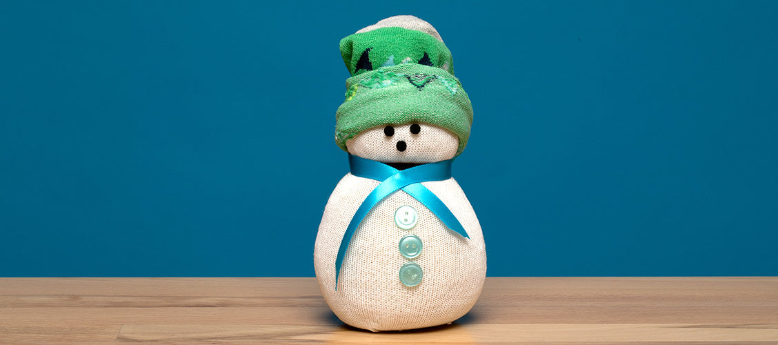 Snowman made out of white and green socks sitting on a craft table - How to Make a No-Sew Sock Snowman