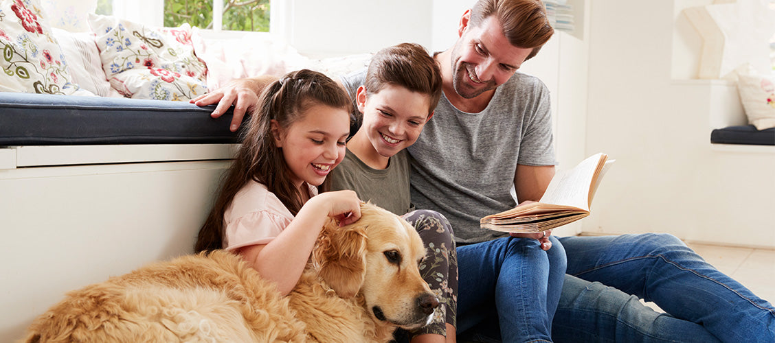 Family sitting on floor reading book with golden retriever dog - Best Pets for Kids