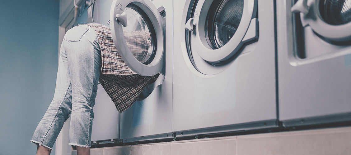 Woman at laundromat looking in washing machine - 8 Places to Find a Lost Sock