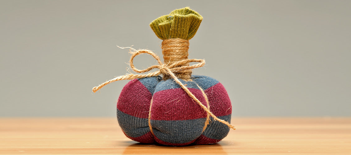 Small pumpkin made out of a sock and twine sitting on a craft table - How to Make a Sock Pumpkin
