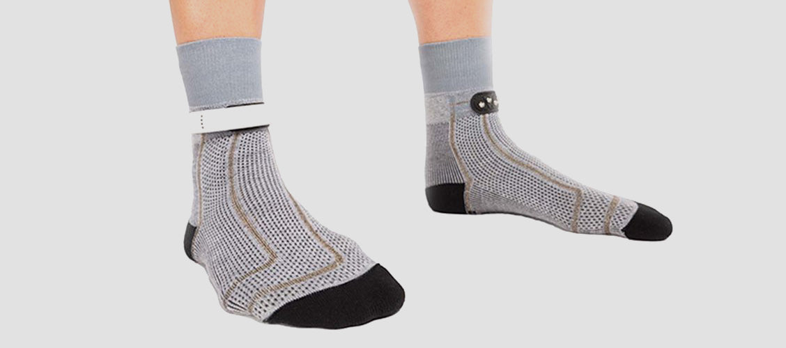 Man wearing gray crew-length smart socks with a sensors on the ankle - 10 Unexpected Socks
