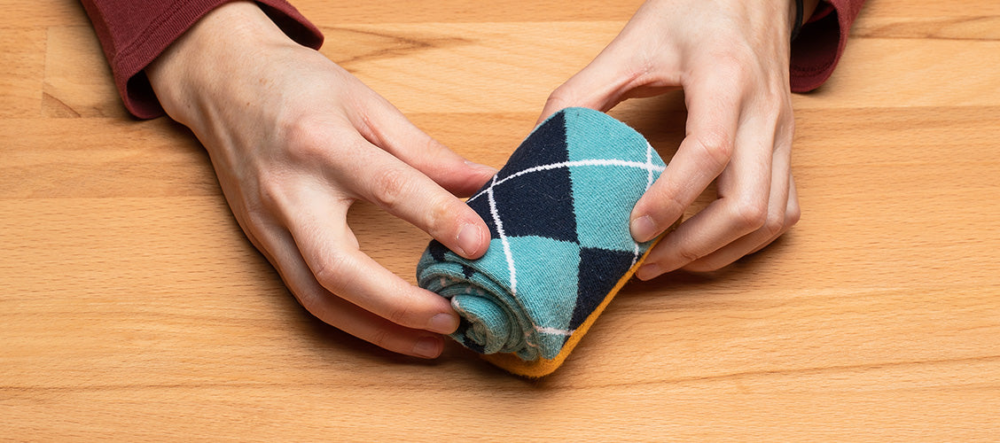 Hands folding argyle socks using the roll method