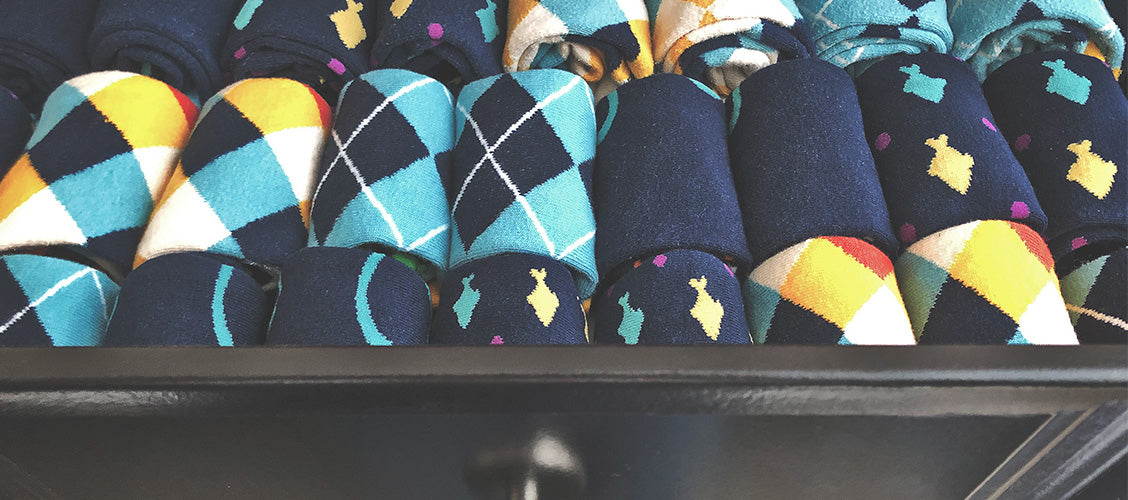 Dresser drawer full of fun socks that are rolled up and placed side by side - 6 Ways to Fold Socks