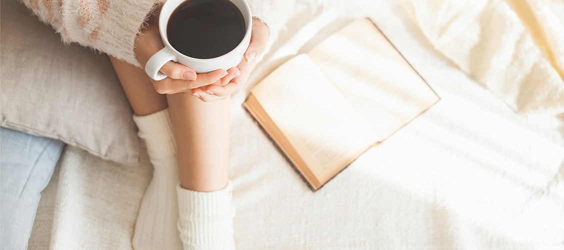 Woman in cream socks holding a warm cup of coffee - 10 Ways to Keep Your Feet Warm