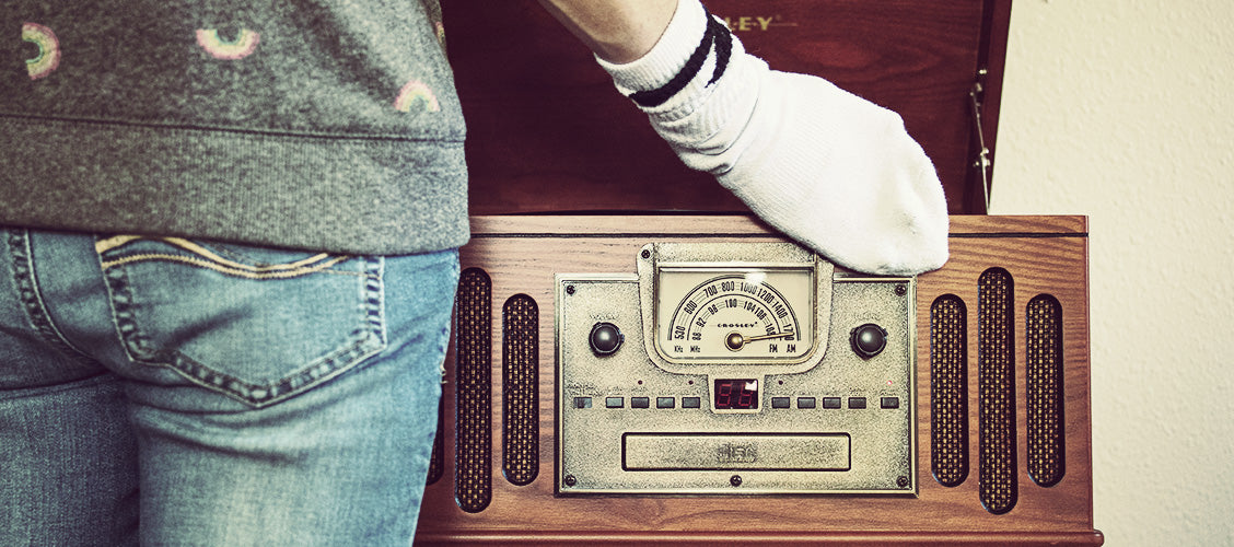 Woman wearing old white sock on hand dusting antique record player - 15 Uses for Old Socks