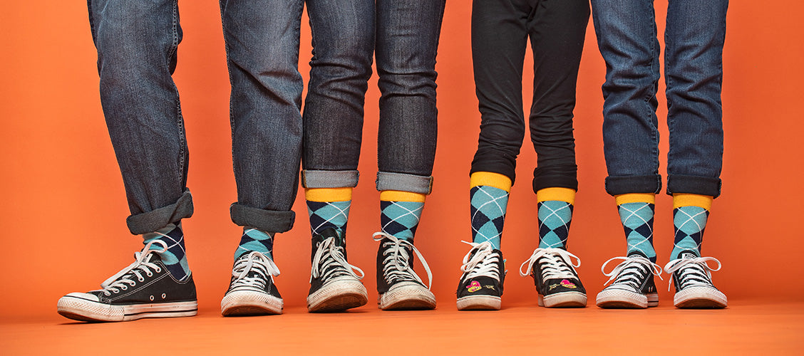 Four people standing next to each other wearing matching socks and shoes - Why Matching is Fun