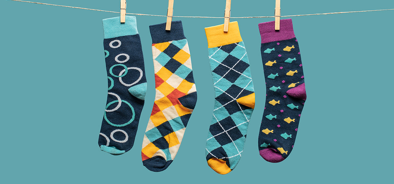 Four pairs of colorful socks hanging on a clothes line - Goldie Socks