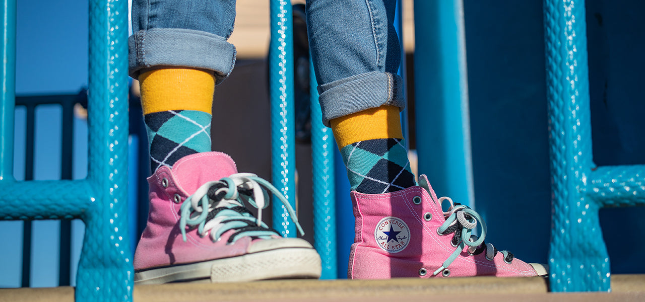 Young girl standing on a playground wearing blue argyle socks and pink shoes