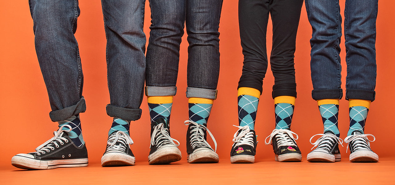 Family of four wearing matching socks with a blue argyle pattern