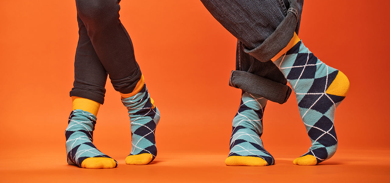 Father and daughter standing with crossed feet wearing matching socks in a blue argyle pattern