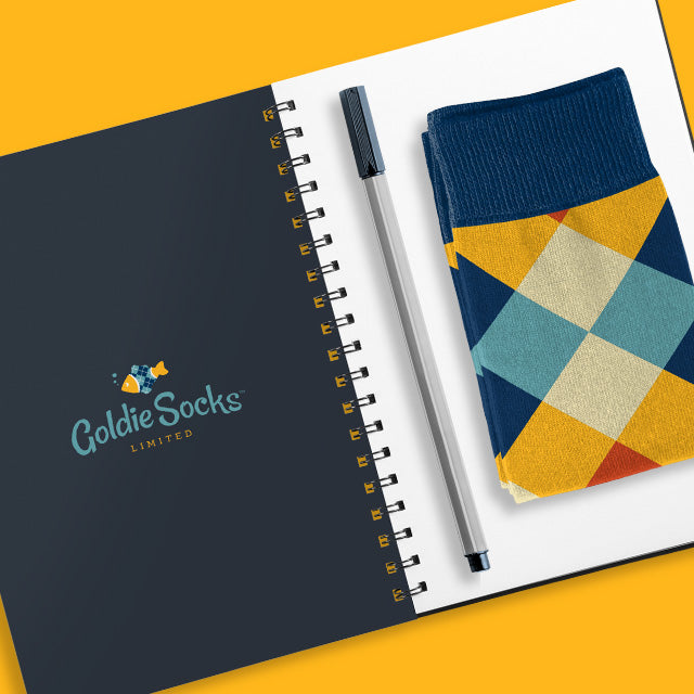 Writing journal with checker socks folded on top next to pen - Goldie Socks