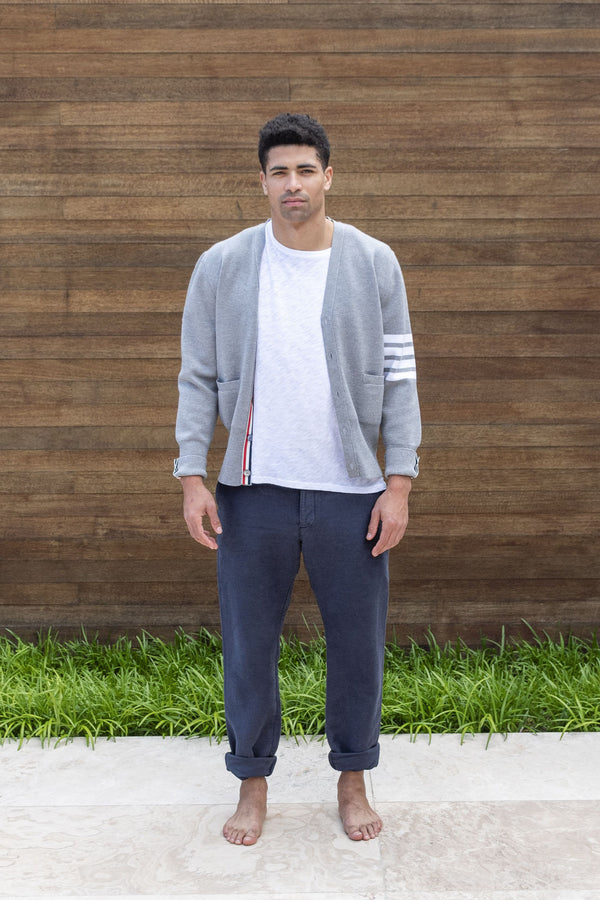 Man modeling grey Milano Stitch Cardigan with 4 white bars on middle right sleeve, in front of outdoor vintage wooden wall