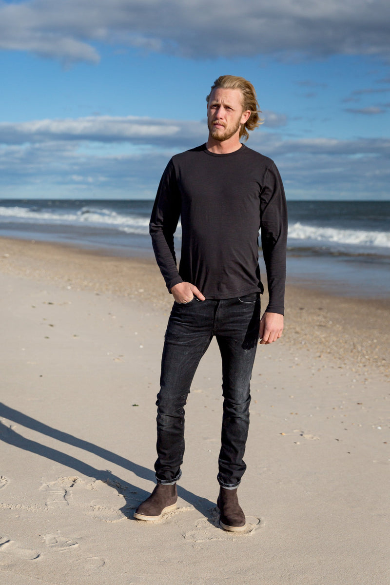 Man modeling a Standard Slub Long Sleeve Tee in black on beach