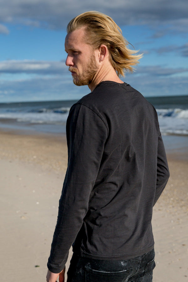 Man modeling the back of Standard Slub Long Sleeve Tee in black, on the beach