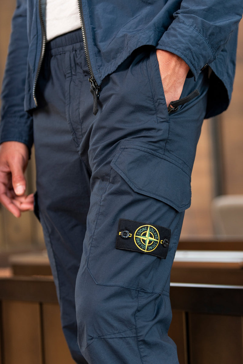 Man modeling 5-Pocket Trousers with Elastic Cuffs in Blue Marine close up from the side, in wood paneled room