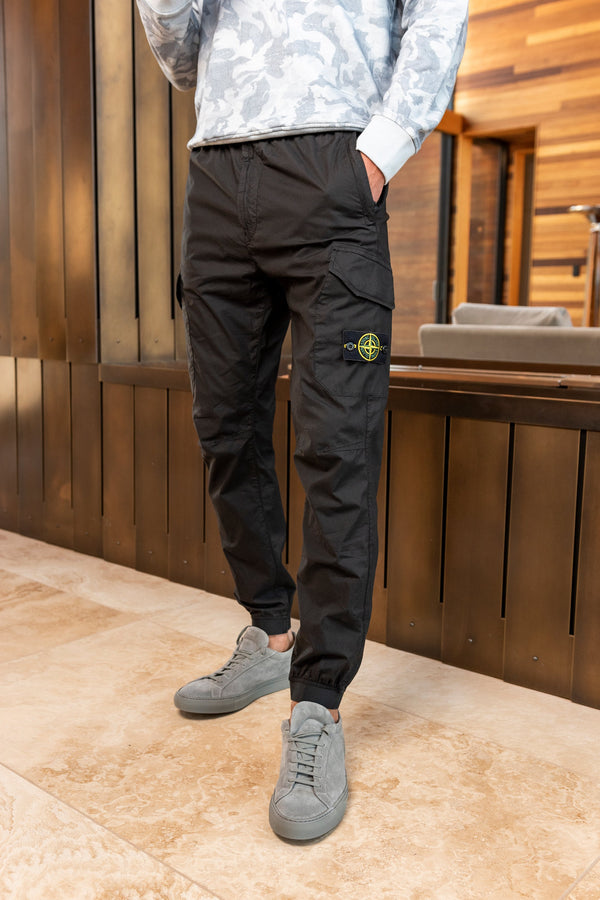 Man modeling Stone Island 5 Pocket trousers with grey shoes and white camo top, inside a wood walled cabin