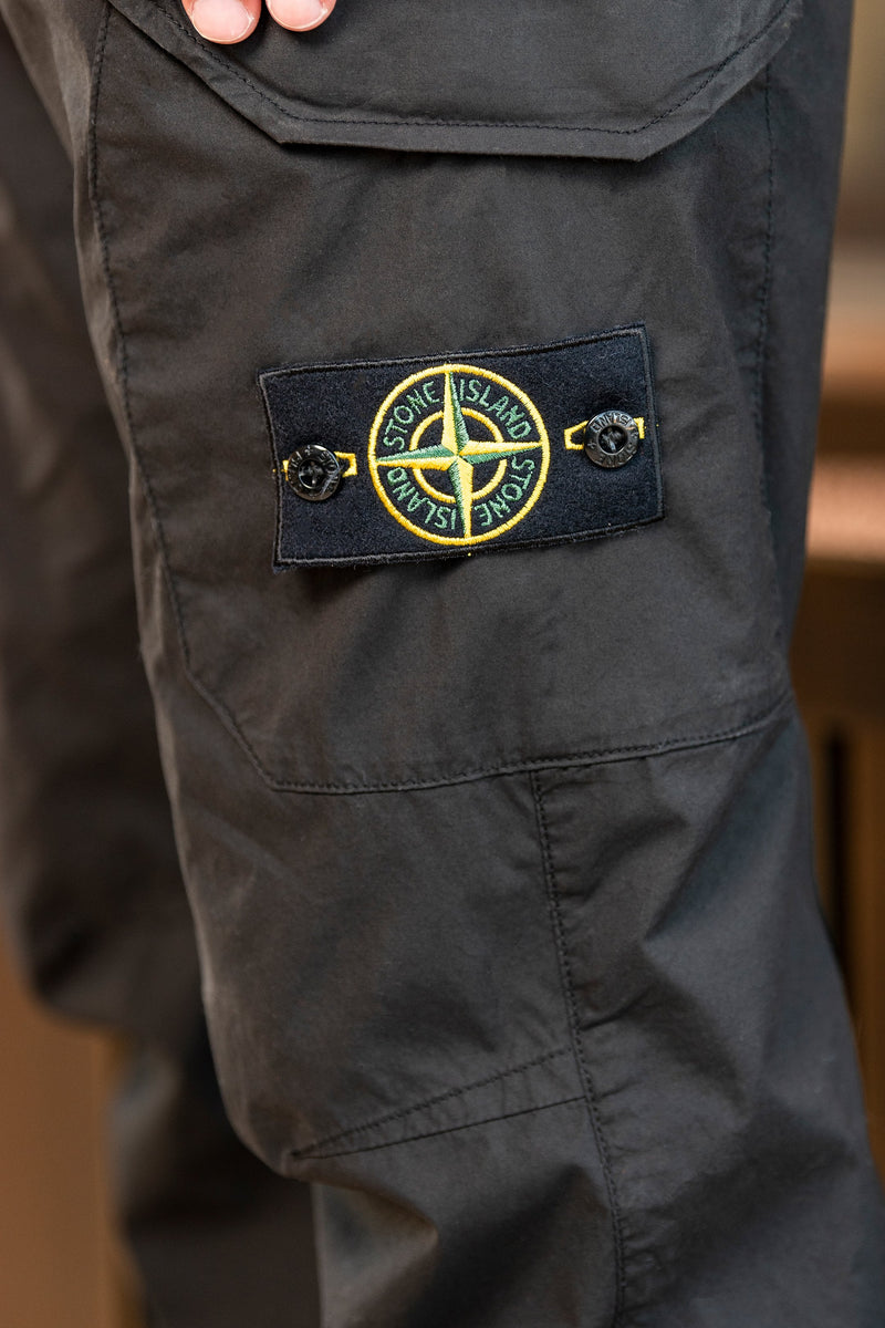 Man modeling Stone Island 5 Pocket trousers logo on side of left leg, inside a wood walled cabin