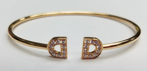 "18KT ROSE GOLD BANGLE BRACELET WITH ""D"" SHAPED DIAMOND ELEMENTS ON ENDS"
