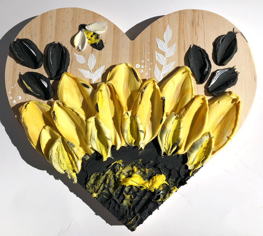 Wooden heart and giant sunflower with bee