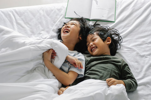Two siblings lie in bed together with a book, laughing