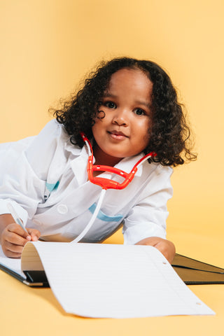A child in a doctor's white coat revises her notes