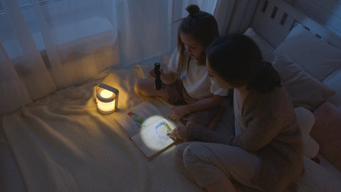 A mother and child read a book together with a flashlight in bed