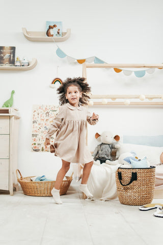 A little girl jumps around in her room.