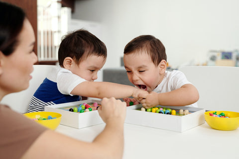 Two little boys plays with toys together, while one child tries to bite his brothers' hand