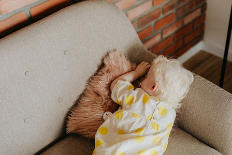 A toddler sleeps face down on a couch