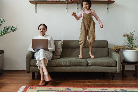 A child jumps on the couch while her mom tries to work