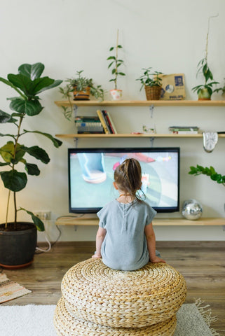 A girl sits watching TV