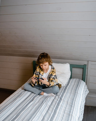 A child sits in his bed on his phone