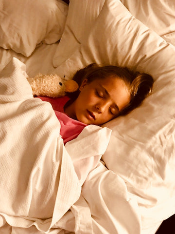 A child sleeps soundly in a bed