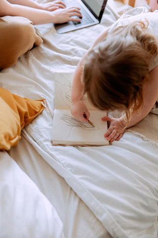 A child scribbles on a notebook while her parent works next to her