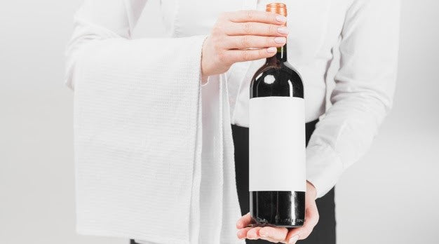 A man is holding a bottle of wine