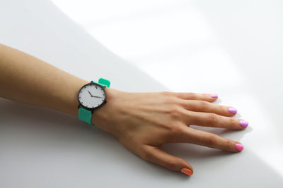 mint green silicone watch with matte black watch case on woman's hand. Colourful, neon watch strap in mint green.