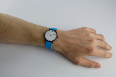 neon blue silicone watch with matte black watch case on man's hand. Colourful, neon watch strap in neon blue.