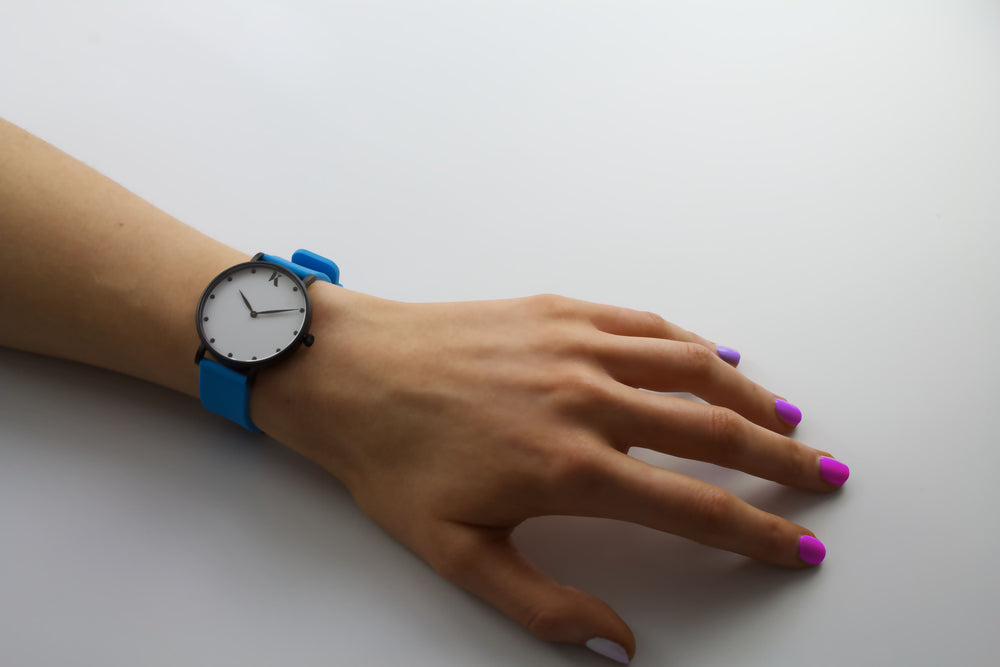 neon blue silicone watch with matte black watch case on woman's hand. Colourful, neon watch strap in neon blue.