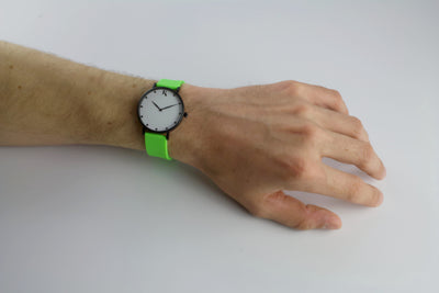 Neon green silicone watch with matte black watch case on man's hand. Colourful, neon watch strap in neon green.