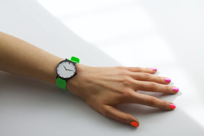 Neon green silicone watch with matte black watch case on woman's hand. Colourful, neon watch strap in neon green.