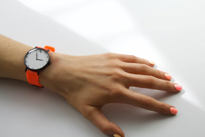 neon orange silicone watch with matte black watch case on woman's hand. Colourful, neon watch strap in neon orange.