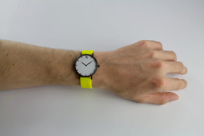 Neon yellow silicone watch with matte black watch case on man's hand. Colourful, neon watch strap in neon yellow.