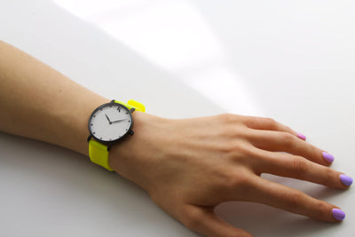 Neon yellow silicone watch with matte black watch case on woman's hand. Colourful, neon watch strap in neon yellow.
