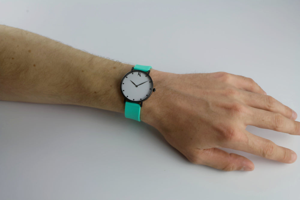 mint green silicone watch with matte black watch case on man's hand. Colourful, neon watch strap in mint green.