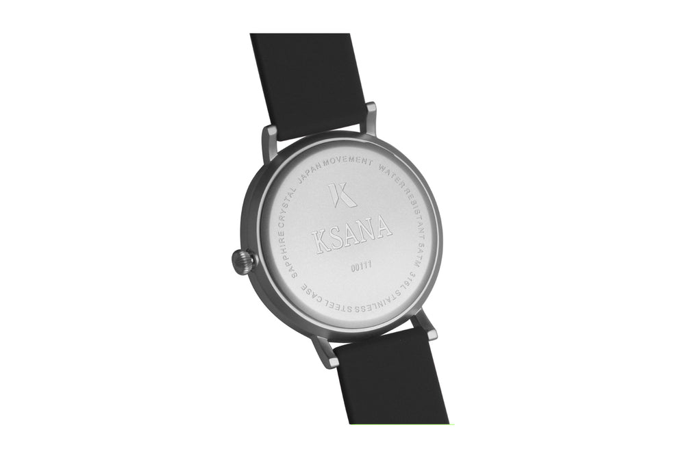Black and silver watch. Ksana engraved on the reverse along with a unique serial number. Vegan silicone watch strap with minimalist watch face design.