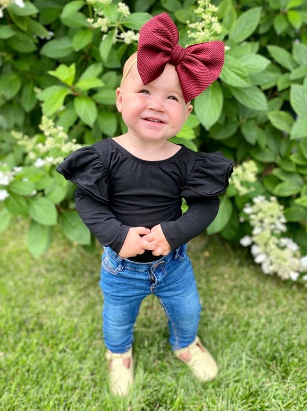 Baby outside with Burgundy big bow in black flutter leotard and blue jeans