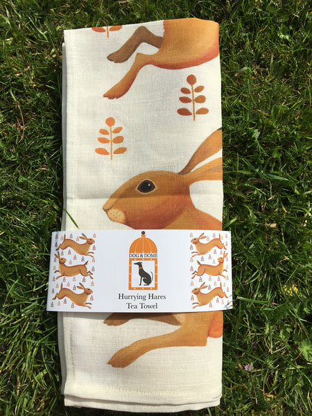 A linen/cotton blend tea towel depicting three hares running through a field of flowers in wrap around packaging