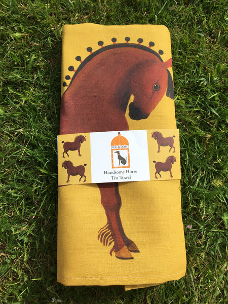 A linen/cotton blend tea towel depicting horses on a yellow ochre background with wrap around packaging